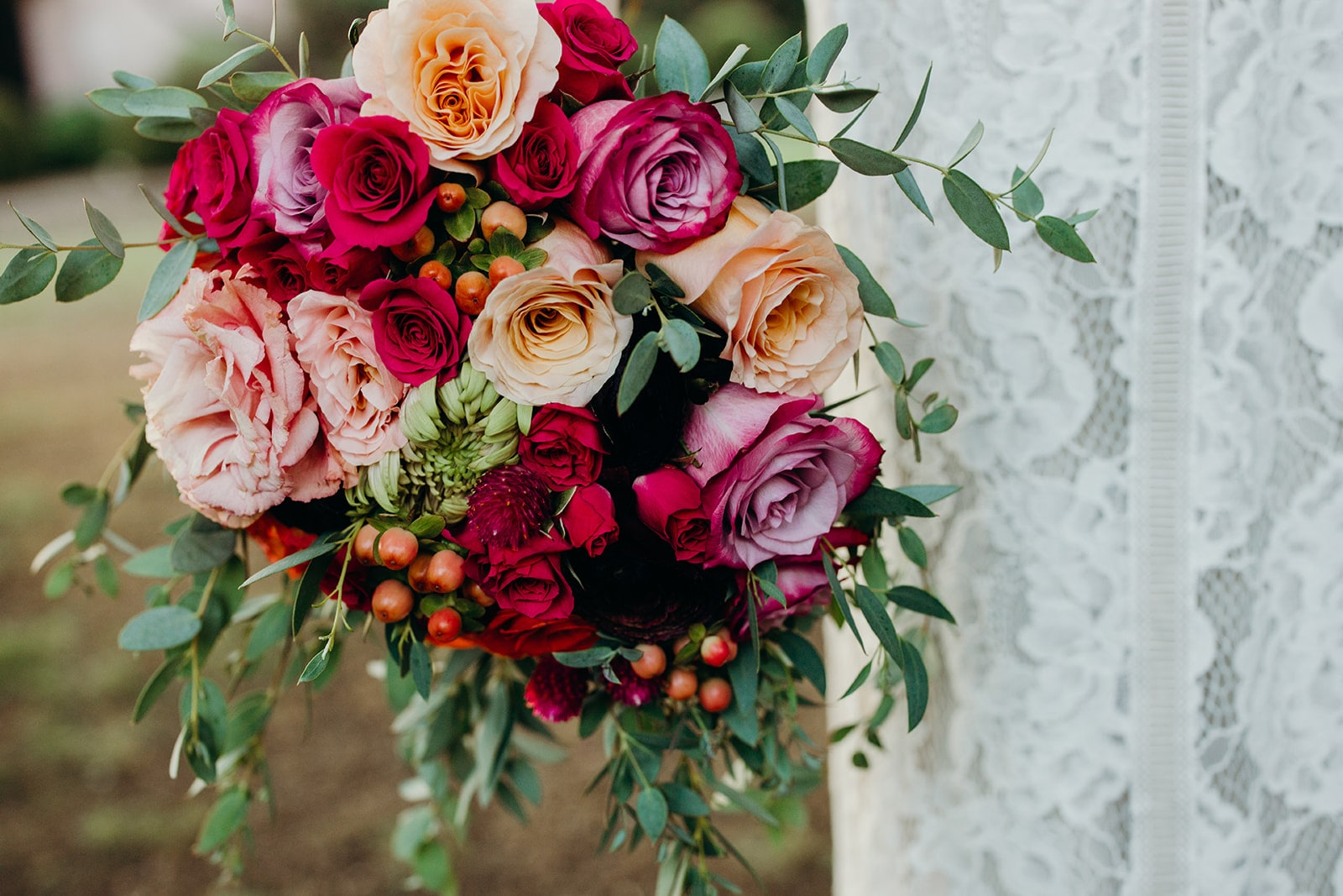 close up of a bride with red bouquet