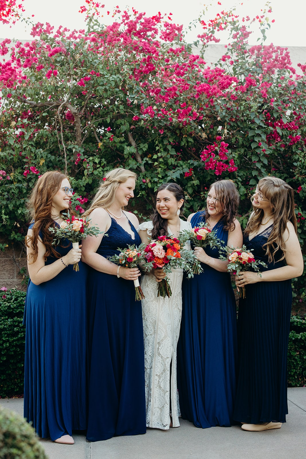 bridesmaids and bride with red bouquets