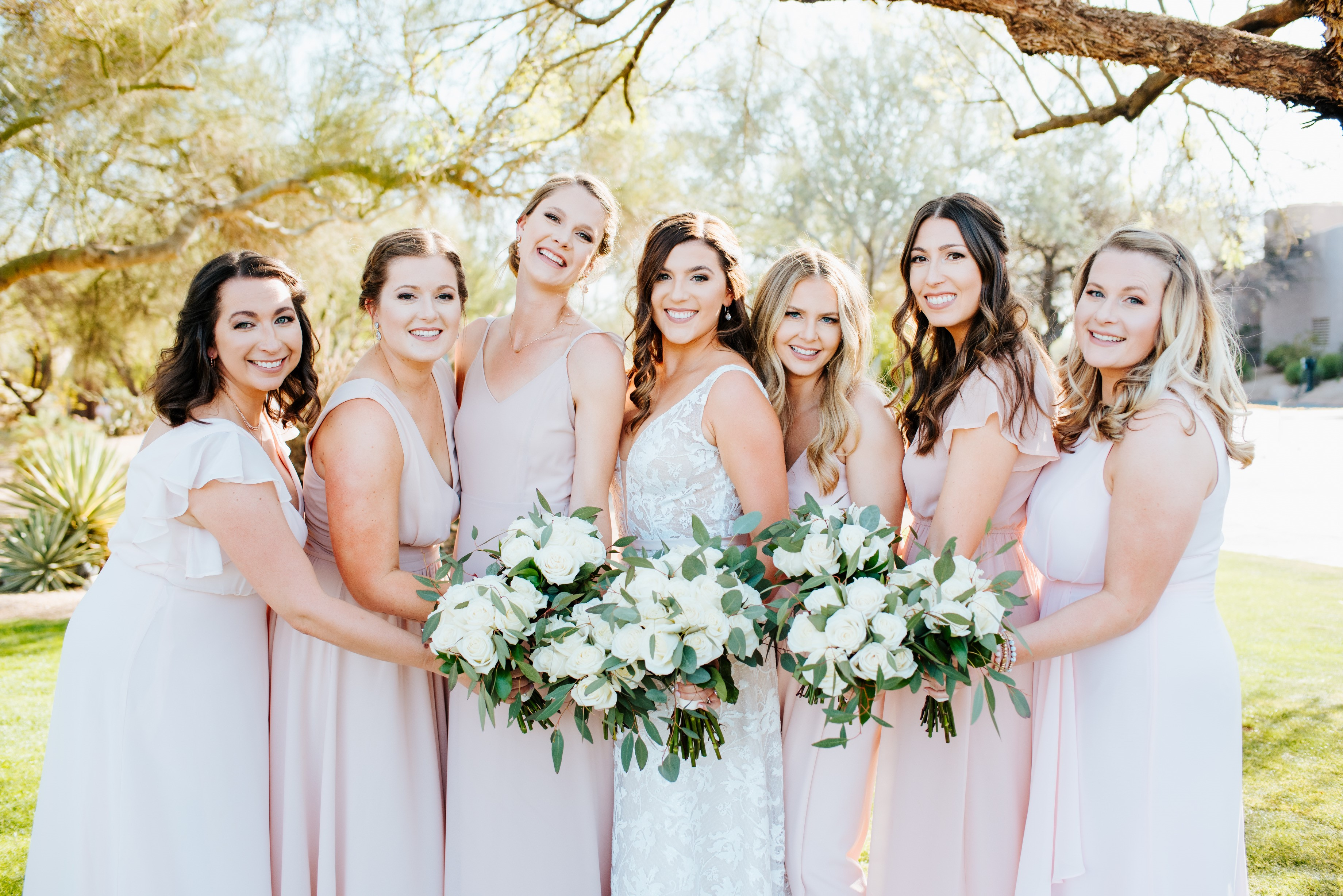 bridesmaids posing with bouquets held together