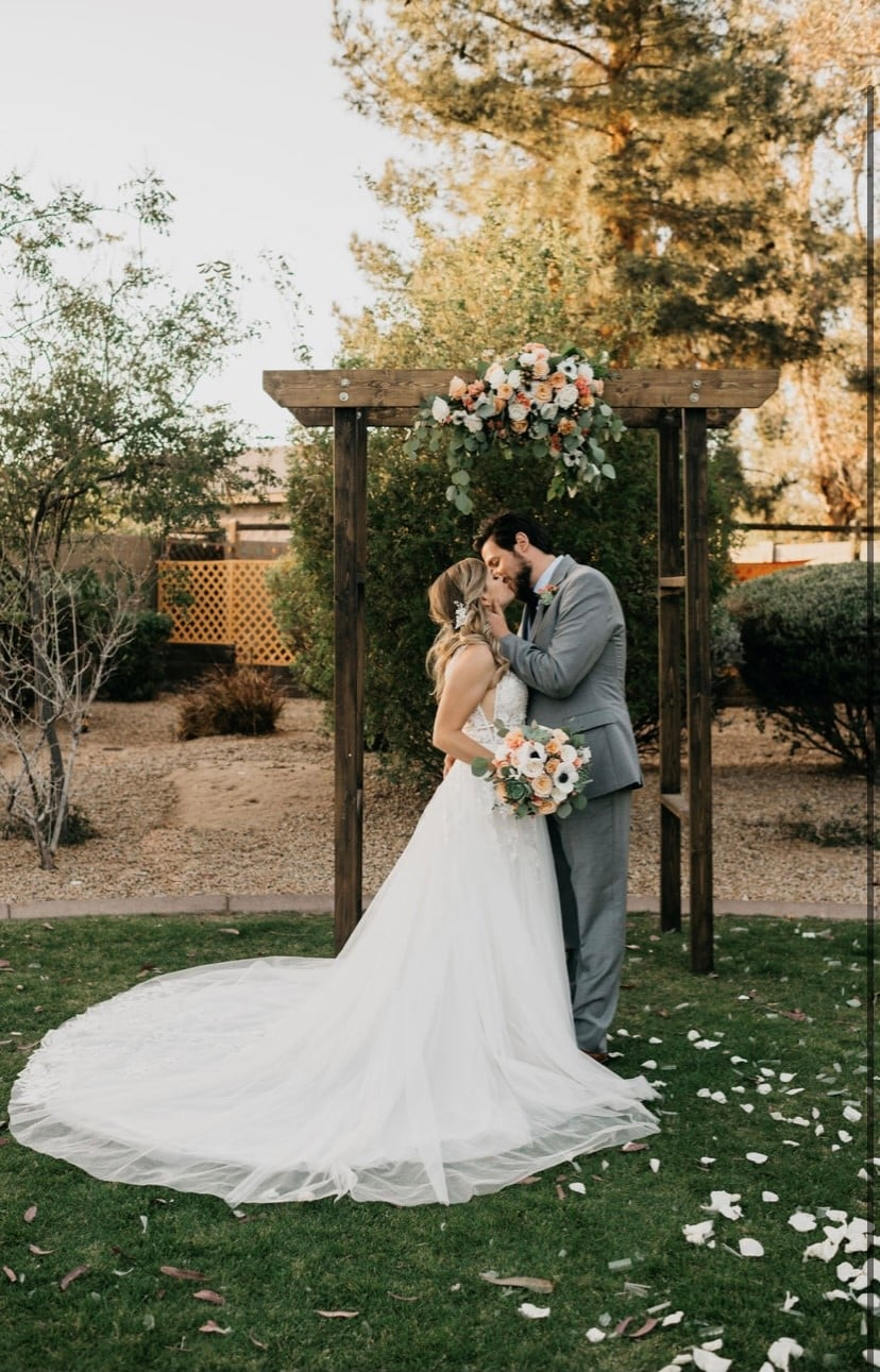 Bride and grooming kissing in front of wedding arch