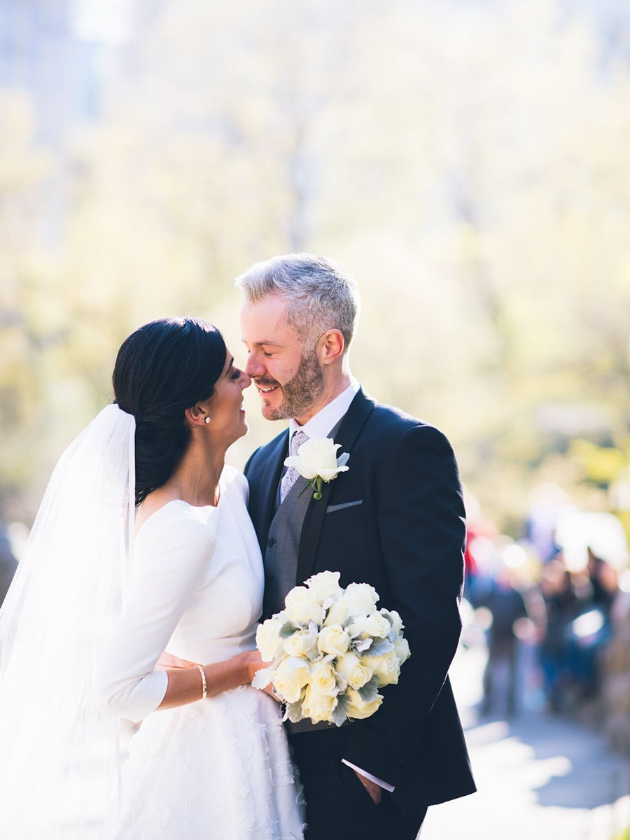 Newly wed couple kiss with flowers in hand