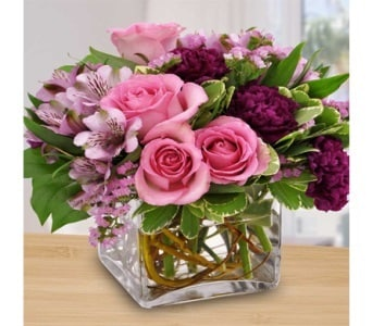 Bouquet of fresh flowers in delectable shades of raspberry, lavender and pink roses and alstroemeria lilies in vase