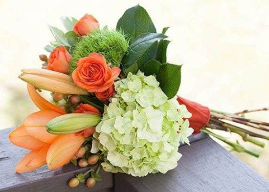 Hand-tied bouquet of orange and green flowers