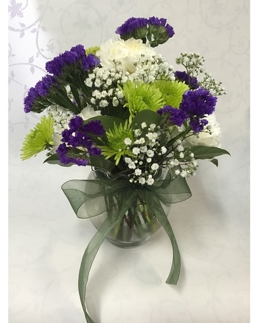 Pee Vase Of Green Purple And White Flower Arrangement