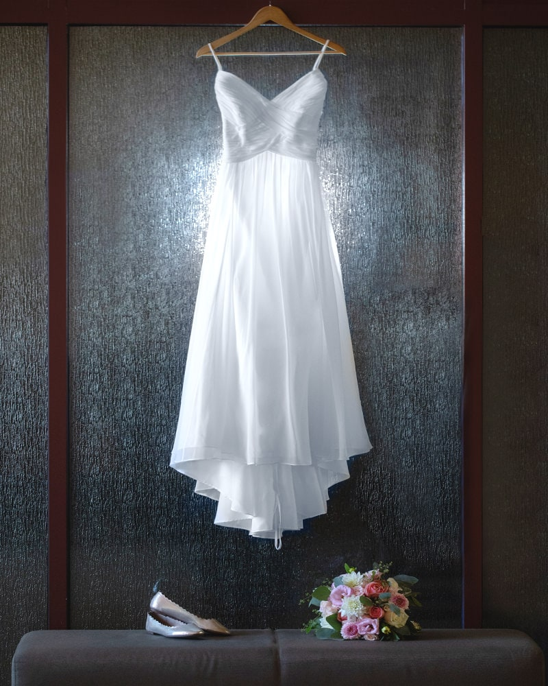 elegant image of wedding dress hanging near shoes and bridal bouquet before the service