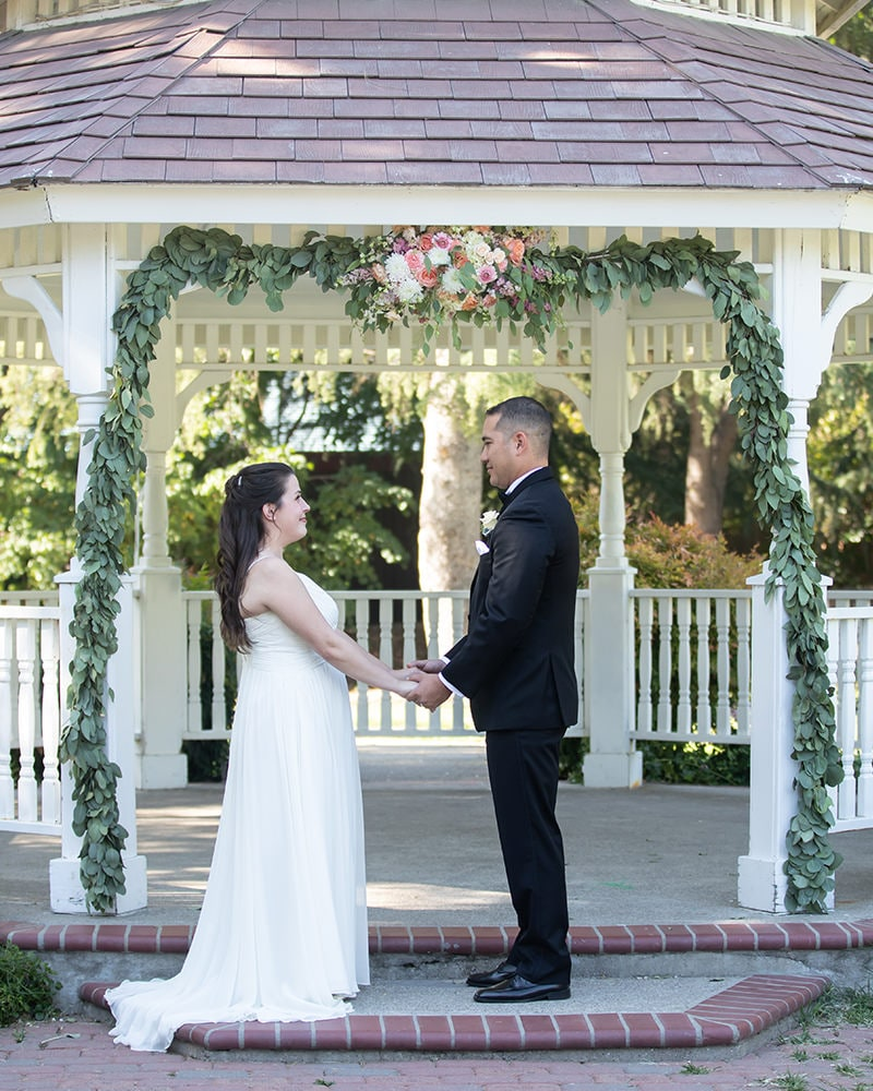 bride and groom stand holding hands beneath floral wedding arch