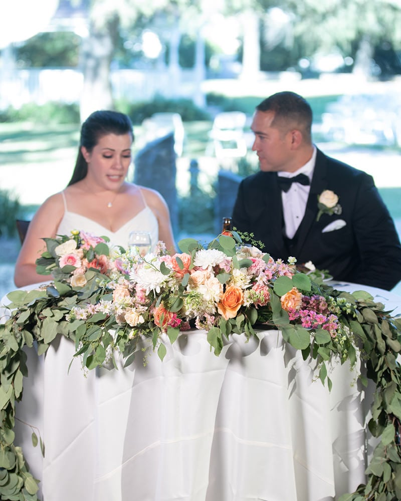 bride and groom sit together at the reception, framed by beautiful wedding flowers