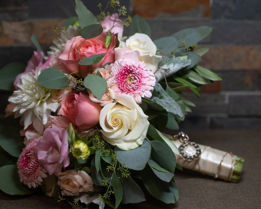 wedding bouquet resting against a dark wood background
