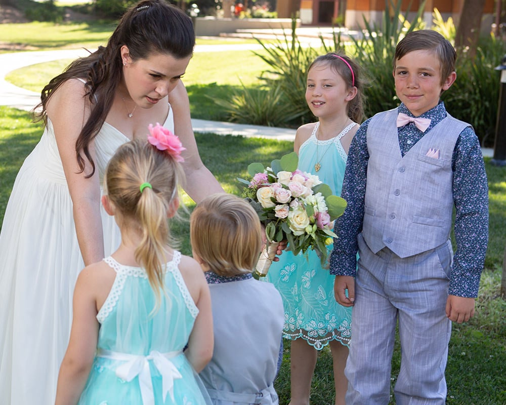 bride leans over to talk to gathered children