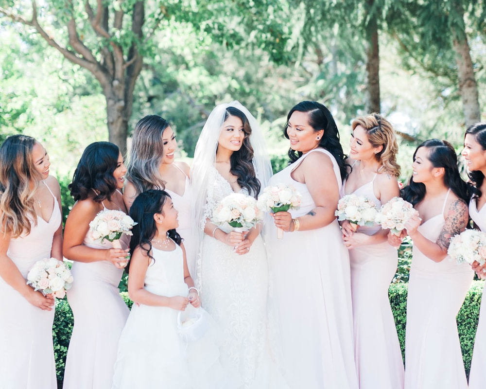 bridal company surround the bride with bouquets in hand