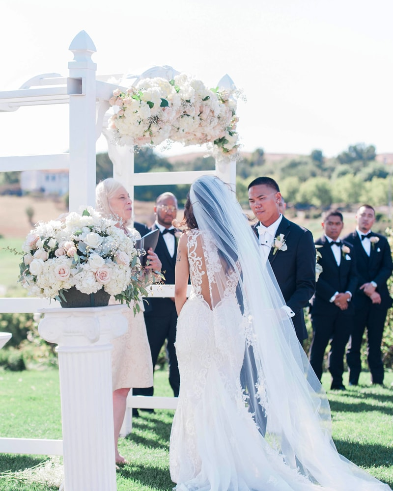 bride and groom stand beneath a floral wedding arch