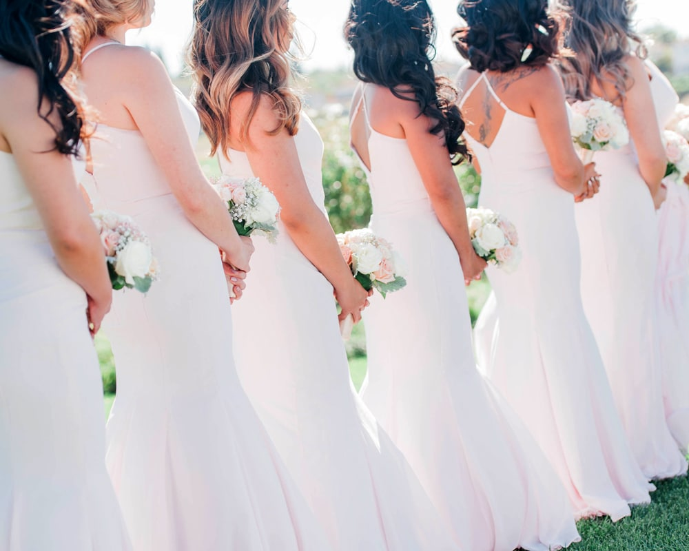 bride's maids stand in line with flowers in hand