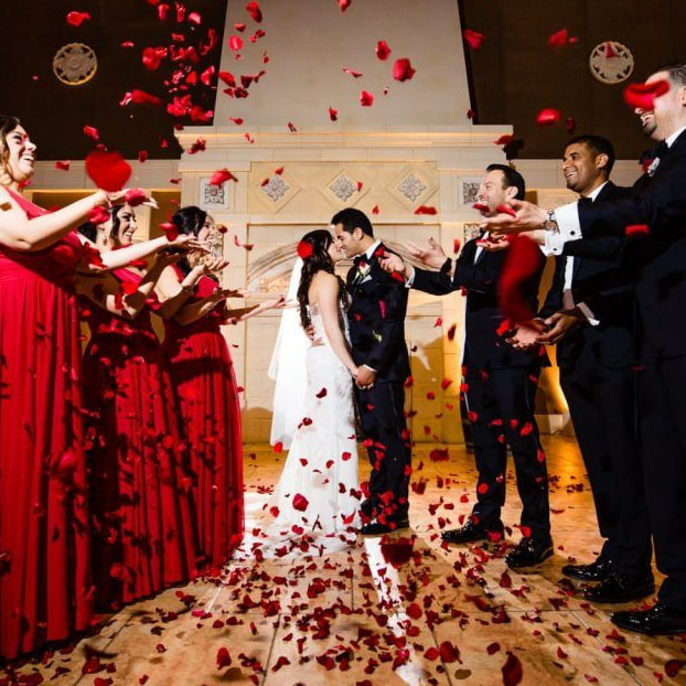 wedding flowers being tossed behind a newlywed couple
